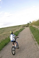 Boy 8_9 cycling on road in countryside