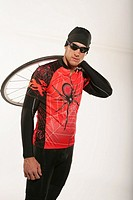 Studio shot of male cyclist holding bicycle wheel
