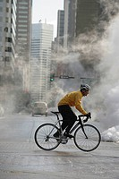 Man cycling in steamy street during winter