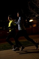 Two young women running on sidewalk at night