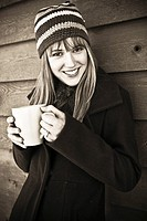 Young woman in winter clothing holding mug