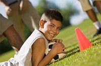 Boy 13_15 lying down on grass holding soccer ball.