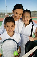Mother with son and daughter by net on tennis court portrait