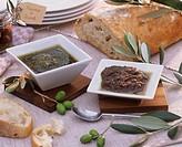 Basil_ & tomato pesto in small dishes with olives, ciabatta