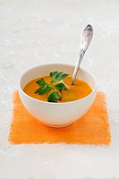 Pumpkin soup with croutons and parsley in a bowl
