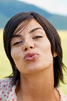 Woman standing in mountain field Blowing Kiss portrait close up
