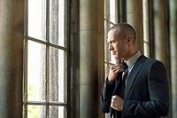 Businessman Adjusting Tie by window