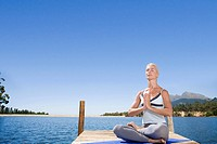 Woman meditating on lake dock (thumbnail)