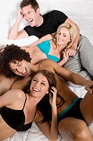 Close_up of four friends enjoying in the bedroom