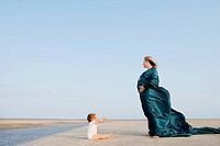 Side profile of a pregnant woman standing on the beach with her baby girl sitting in front of her