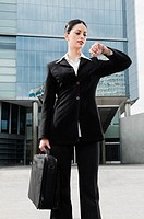 Businesswoman holding a bag and checking the time