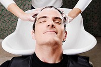 Mid adult man getting hair shampooed at salon