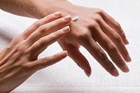 Close_up of a woman´s hands applying lotion