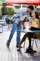 Young couple looking at each other and smiling at a sidewalk cafe