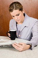 Businesswoman reading a newspaper and holding a coffee cup