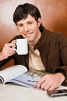 Young man drinking coffee in a cafe and smiling