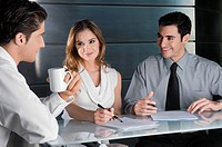 Two businessmen and a businesswoman talking in an office