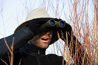 Mid adult man looking through binoculars in a forest