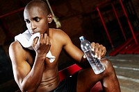 Close_up of a male boxer holding a water bottle and thinking