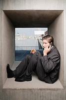 Side profile of a businessman sitting on a window sill and talking on a mobile phone