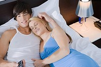 High angle view of a young couple lying on the bed and watching television
