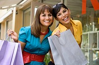 Portrait of a mature woman holding shopping bags and smiling with her daughter