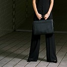 Low section view of a businesswoman holding a briefcase