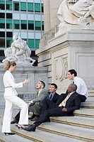 Side profile of four businessmen and a businesswoman discussing on steps