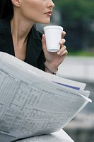 Close_up of a businesswoman holding a disposable cup and a newspaper
