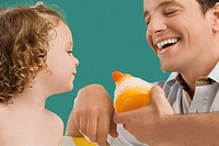 Close_up of a mid adult man looking at his daughter and smiling