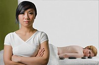 Close-up of a massage therapist with a mature woman lying on a massage table behind her (thumbnail)