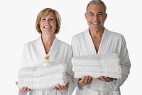 Portrait of a senior man with a mature woman standing together and holding folded towels (thumbnail)