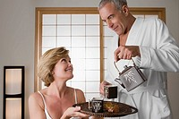 Senior man pouring tea from a tea kettle into the cup with a mature woman holding a tray