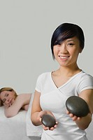 Close_up of a massage therapist holding two pebbles with a mature woman lying on a massage table behind her