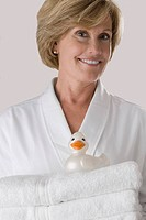 Portrait of a mature woman holding a stack of folded towels