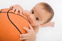 Portrait of a baby boy playing with a basketball