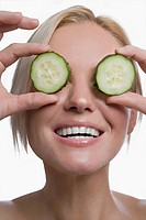 Close_up of a young woman holding cucumber slices in front of her eyes