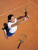 High angle view of a female tennis player jumping with a trophy
