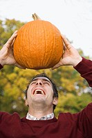 Close_up of a young man holding a pumpkin and laughing
