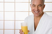 Portrait of a senior man holding a glass of orange juice and smiling