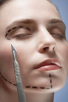 Scalpel near woman´s face with dotted lines, close_up
