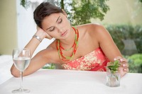 Bored woman playing with plant at dining table