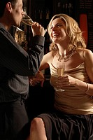 Mid adult couple drinking champagne at bar