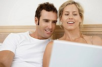 Mid adult couple using laptop in bed
