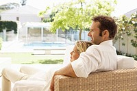 Mid adult couple relaxing on sofa and looking at garden