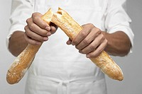 Chef breaking baguette mid section