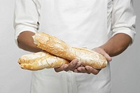 Chef holding two pieces of baguette mid section