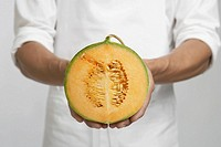 Chef holding half of cantaloupe melon mid section