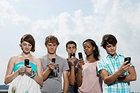 Five teenagers text messaging low angle view
