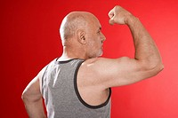 Senior man flexing muscles